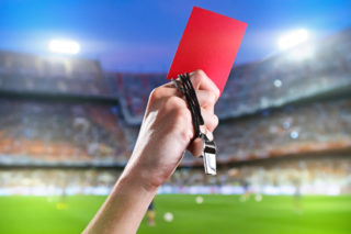 Hand of referee with red card and whistle in the soccer stadium.